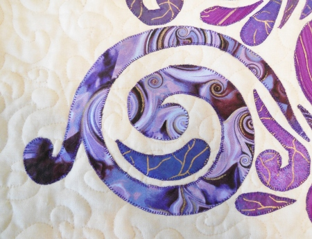 close up of appliqued and quilted purple Christmas tree showing a swirled type of echo quilting